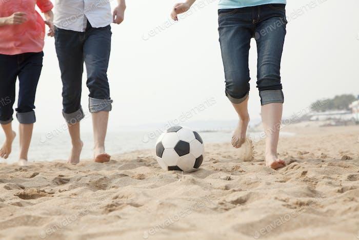 junge Freunde spielen Fußball am Strand