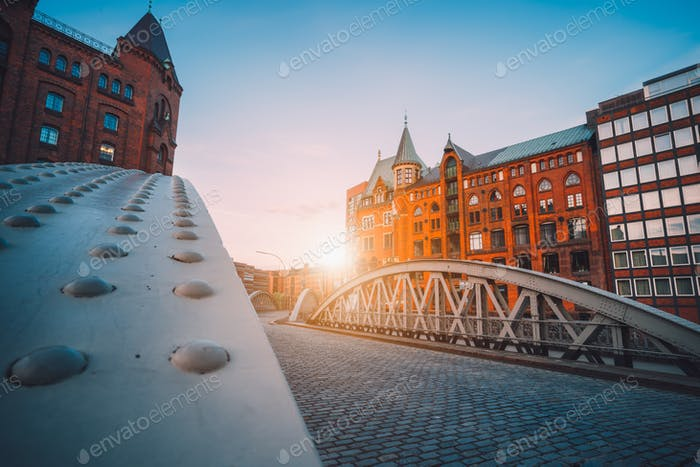 Iron arch bridges in historical warehouses in Speicherstad district in Hamburg, Germany. Backlit sun