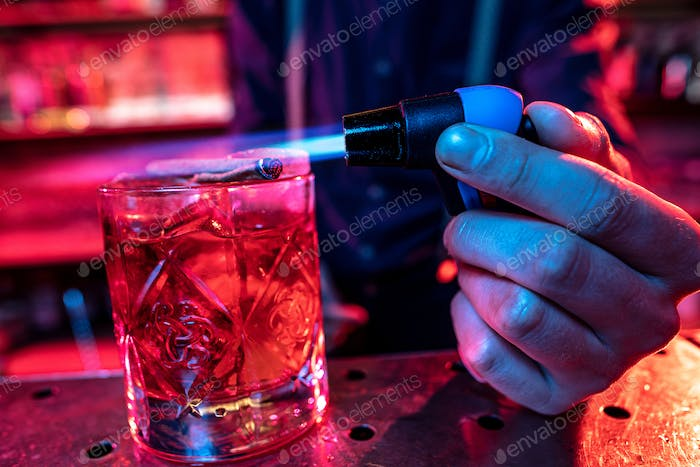 Close up of alcoholic cocktail, beverage, drink in multicolored neon light with fire flame setting