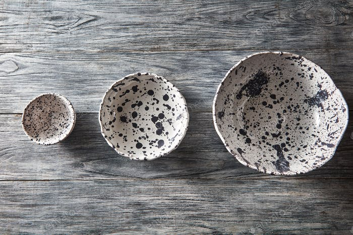 Ceramic bowls of different sizes are empty on a gray wooden background. Flat lay of porcelain dishes
