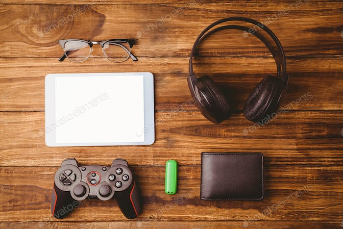 Tablet and glasses next to joystick music headphone and wallet on wooden table