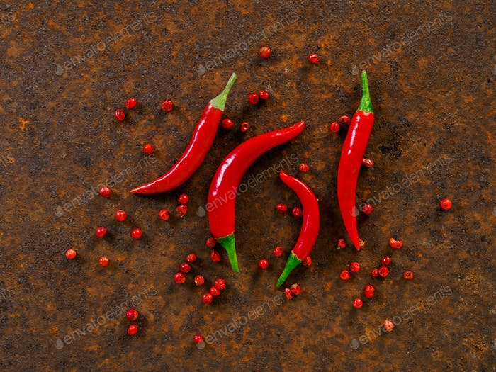 Red hot chili pepper pods and peas on dark metallic rusty background, top view