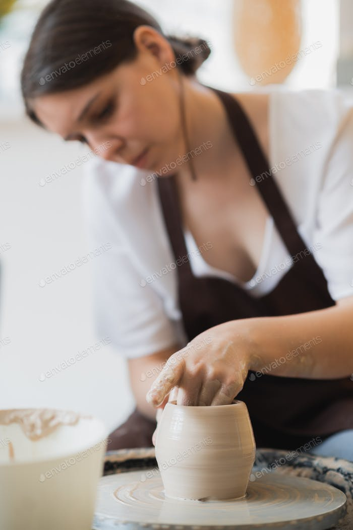 Close-up of potter making pot in pottery workshop. Using sponge and water for moisturizing clay
