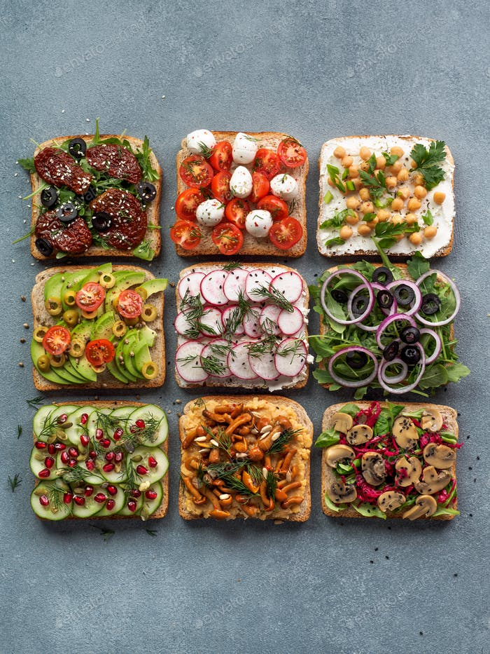 Assortment vegan sandwiches on gray stone background