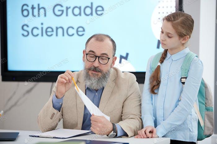 Bärtige Senior Lehrer im Gespräch mit Mädchen in der Klasse
