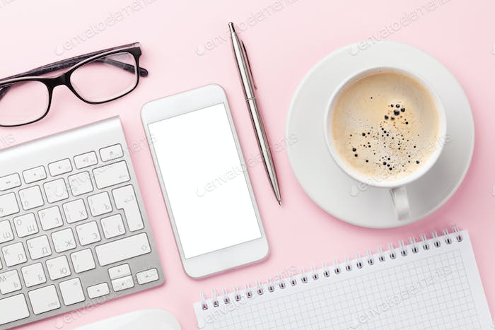 Pink workplace with computer, smartphone and coffee