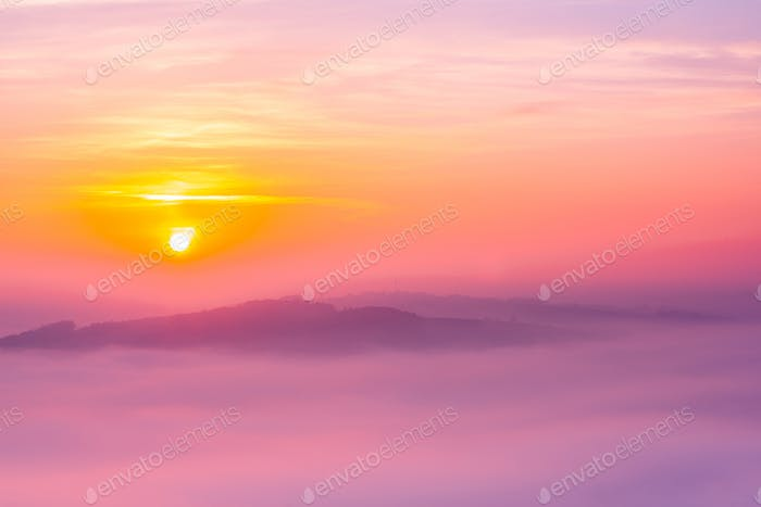 Sun over Clouds at Early Foggy Morning in Autumn