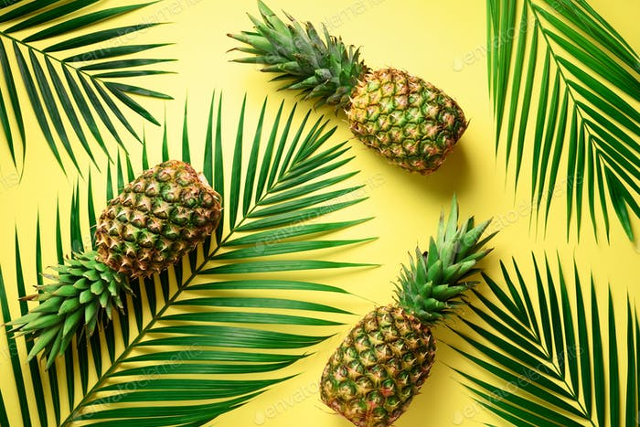 Pineapple and tropical palm leaves on yellow background. Top view. Summer concept. Creative flat lay