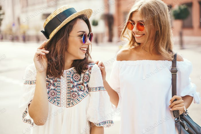 Portrait of two young beautiful women posing outdoors