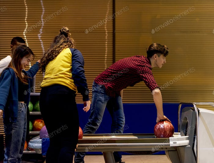 Caucasian boy picking up a bowling ball hobby and leisure concept