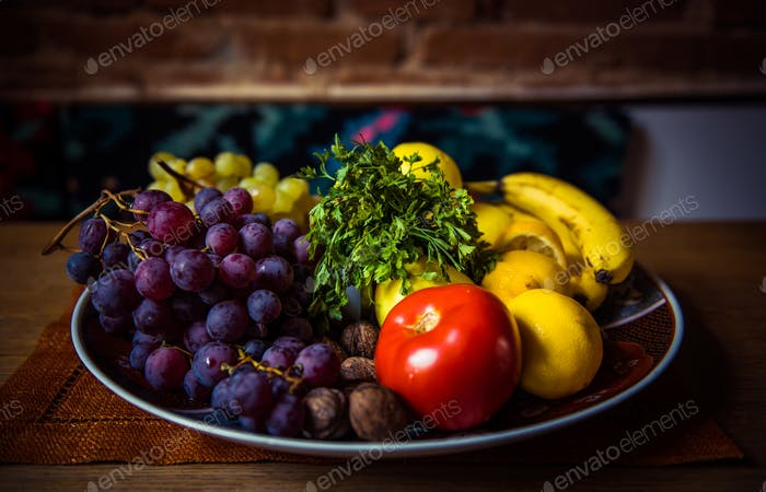 Assortment of juicy fruits in a bowl on wooden table