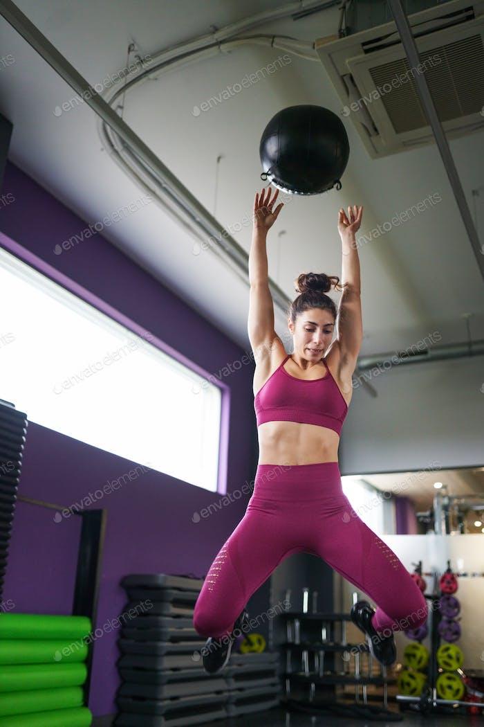 Weibliche Sportlerin Üben Wand Ball Schüsse mit einem med Ball