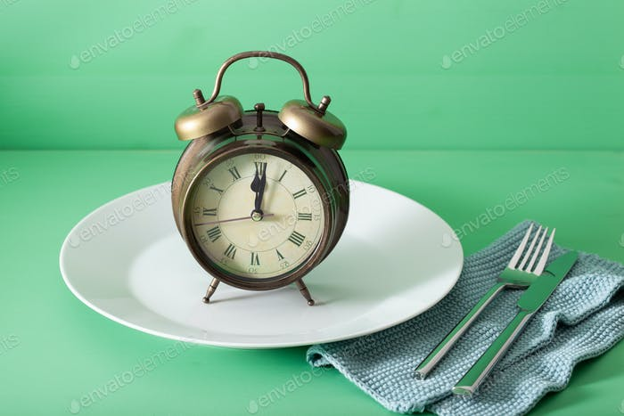 concept of intermittent fasting, ketogenic diet, weight loss. fork alarmclock