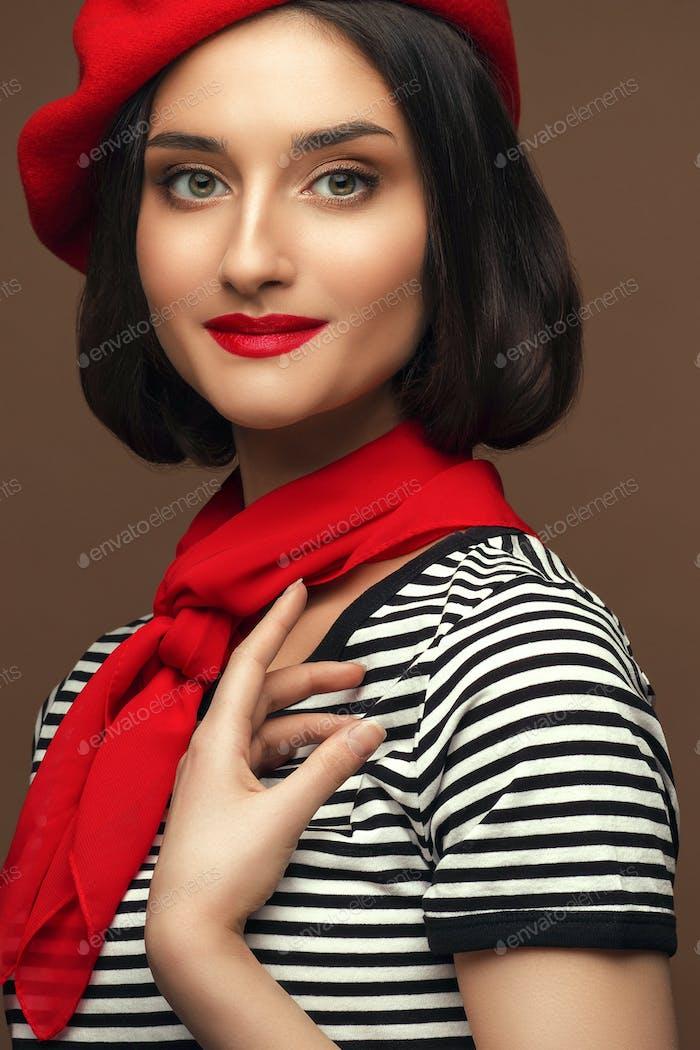 Frau in rotem Baskenmütze und gestreiftes T-Shirt Französisch Stil Brünette. Studio gedreht.