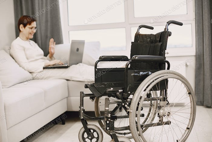 Handicapped woman with lapot lay on couch