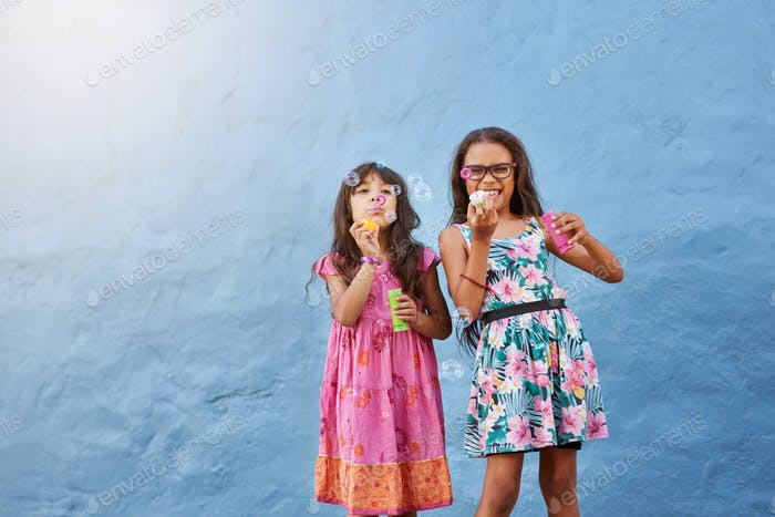 Cute little girls blowing soap bubbles