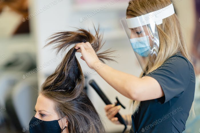 Hairdresser, protected by a mask, combing her client's hair with a hair iron in a salon