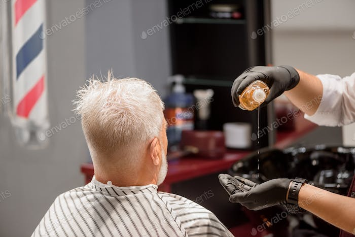 Hands of barber pouring shampoo in hand and old client nearby