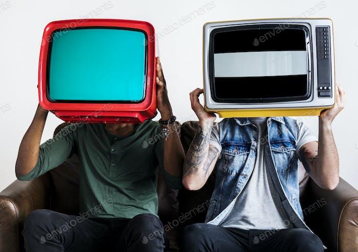 Menschen, die Retro-Fernsehen nebeneinander halten