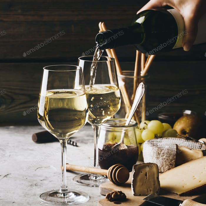 White wine pouring into glasses with charcuterie assortment