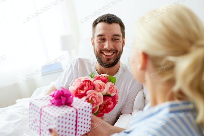 happy couple with gift box in bed at home