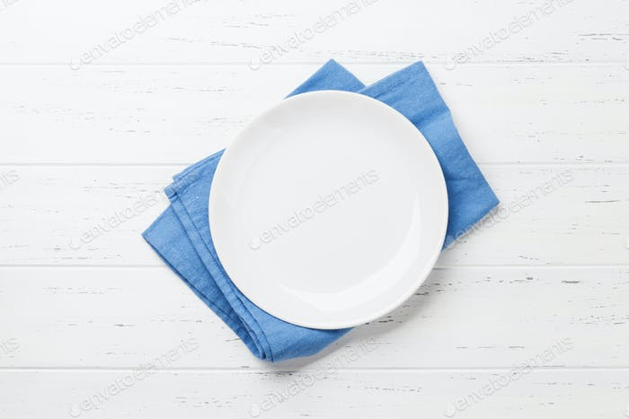 Empty plate on wooden kitchen table