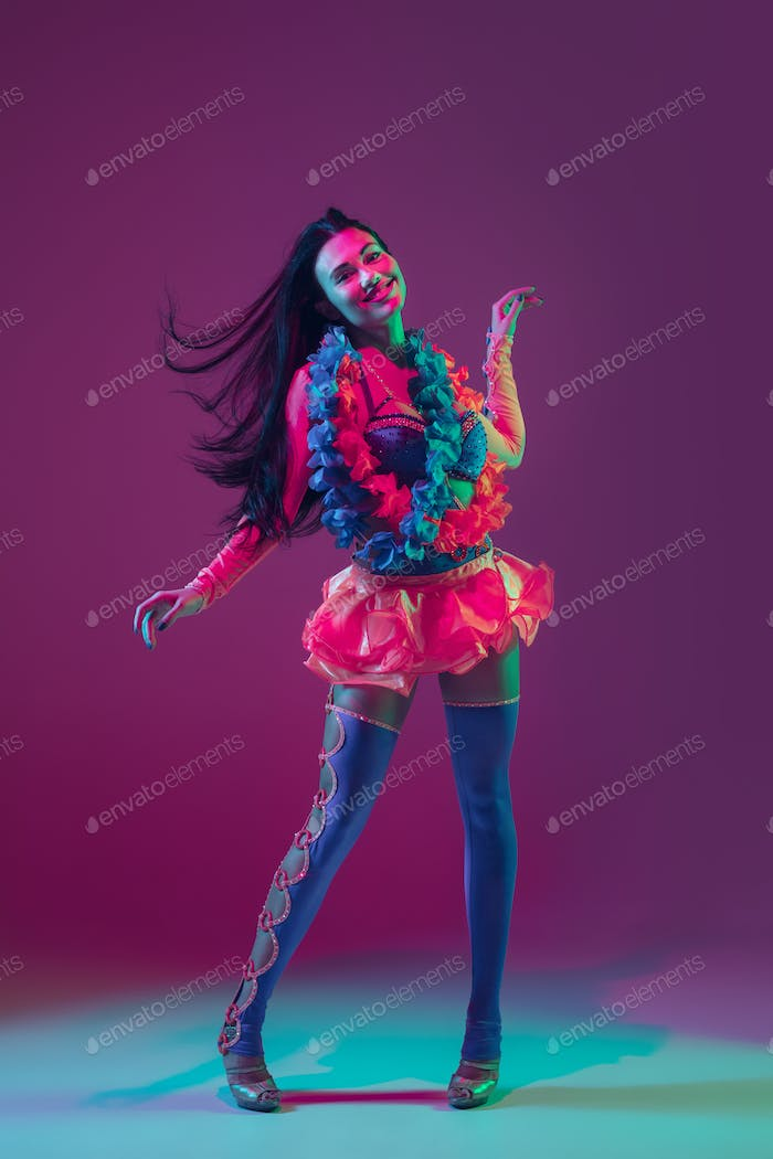 Attractive hawaiian brunette model on purple studio background in neon light