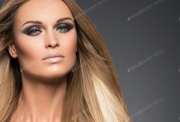 Pelo hermoso largo rubio peinado mujer moda maquillaje saludable piel y pelo fondo negro