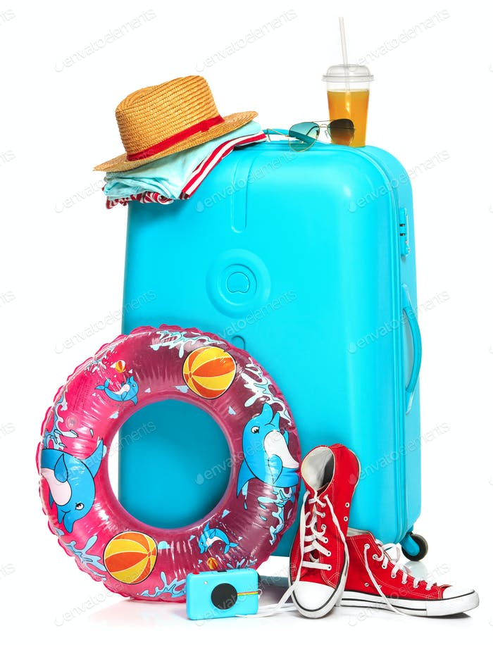 The blue suitcase, sneakers, hat and rubber ring on white background.
