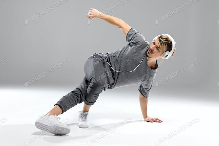 Concentrated young athletic man in headphones dancing on white