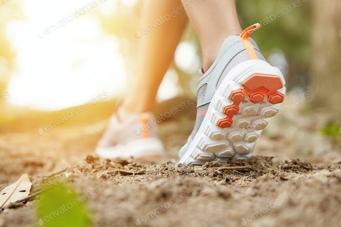 Sports and healthy lifestyle concept. Cropped shot of sporty girl in running shoes as she doing phys