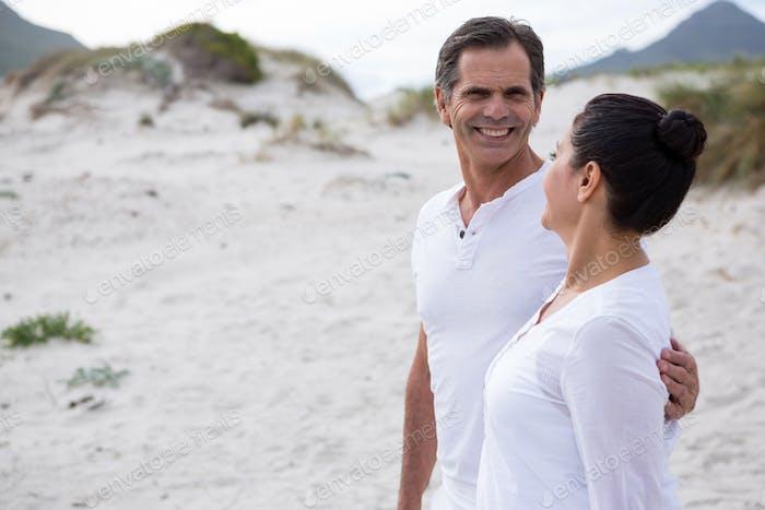 Happy couple standing on beach