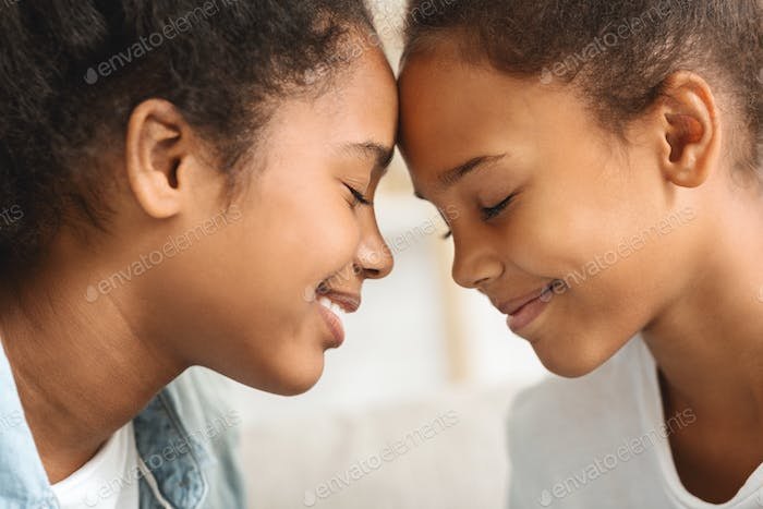 Two girls with eyes closed touching each other with foreheads