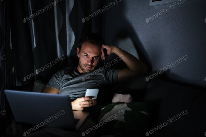 Man sitting on the sofa with a mobile phone and computer