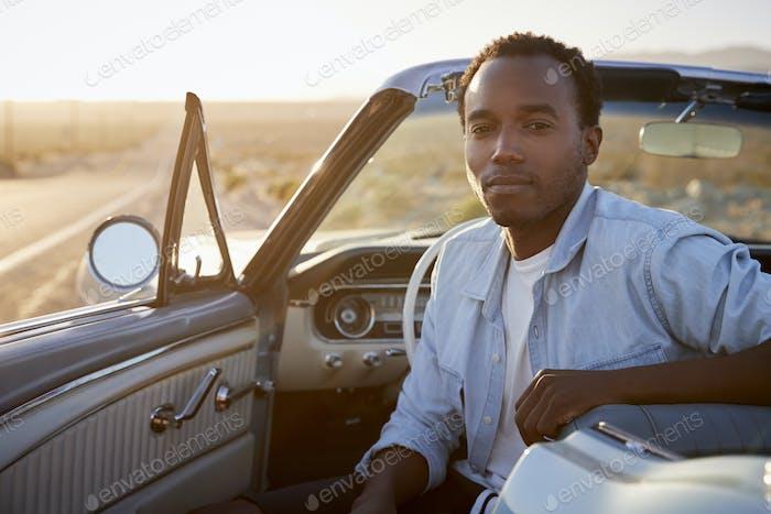 Portrait Of Man Enjoying Road Trip In Open Top Classic Car