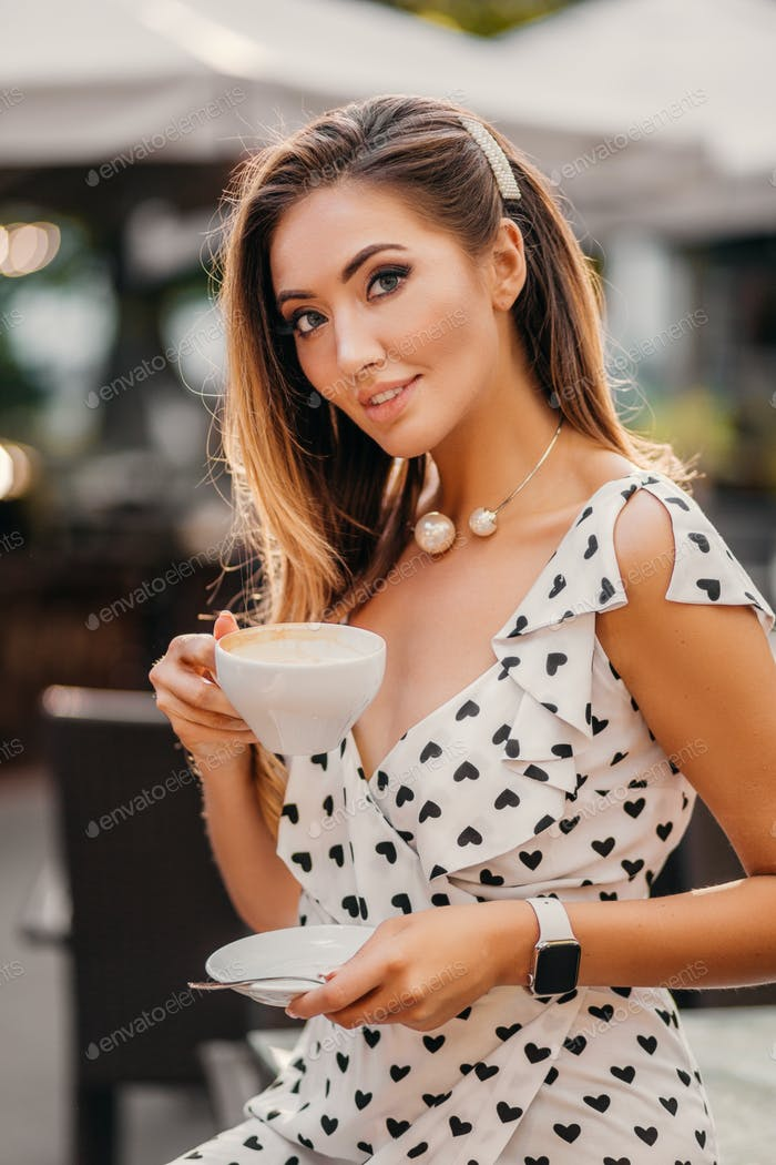 beautiful smiling woman dressed in white printed dress in street cafe