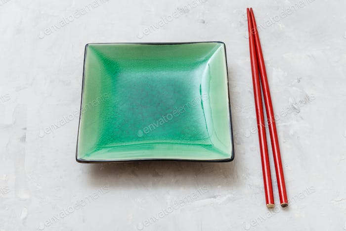 green saucer and red chopsticks on gray concrete