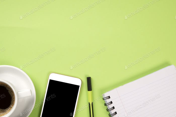 Light green desk with mobile phone, pen, notebook and a coffee