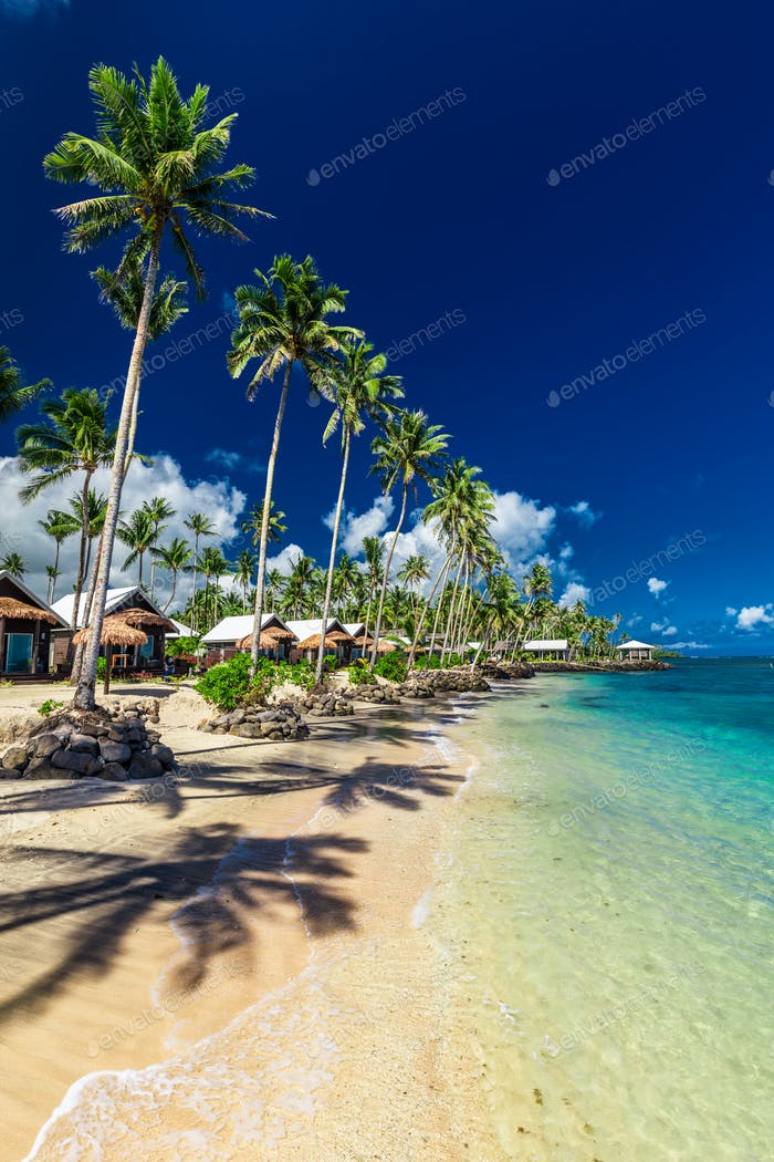 Tropical beach with with coconut palm trees and villas on Upolu,