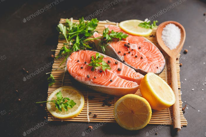 Two salmon steaks with lemon, pepper and salt. View from above.