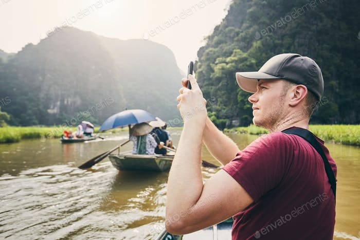 Tourist with mobile phone on boat