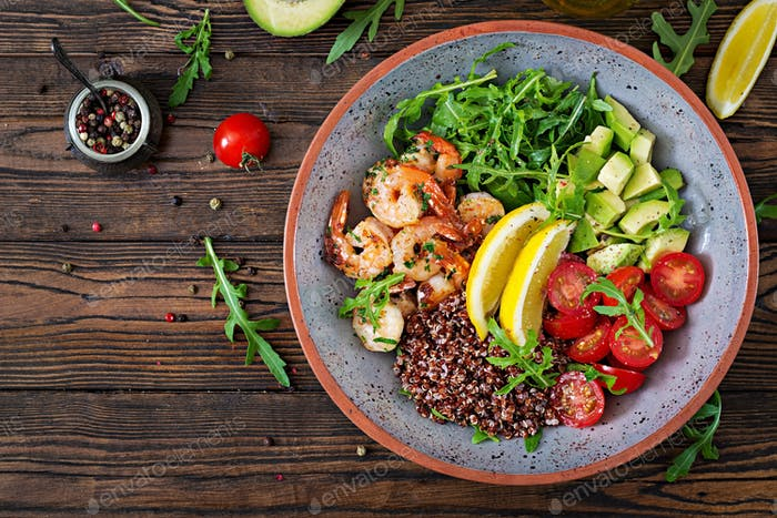 Delicious healthy Buddha bowl with shrimps, tomato, avocado, quinoa, lemon and arugula
