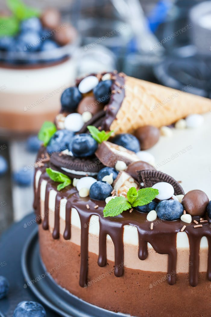Three chocolate mousse cake decorated with waffle cone, fresh bl