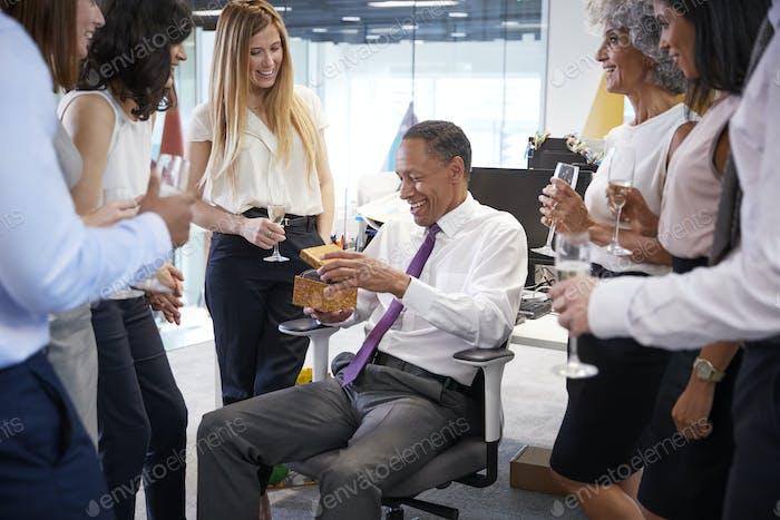 Mitarbeiter feiern den Ruhestand eines Kollegen im Büro