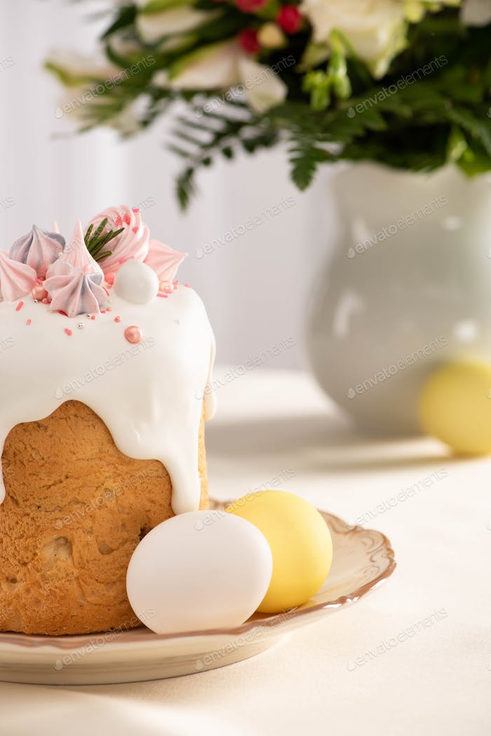 Delicious Easter Cake Decorated With Meringue Near Colorful Eggs on Plate on Table With Flowers