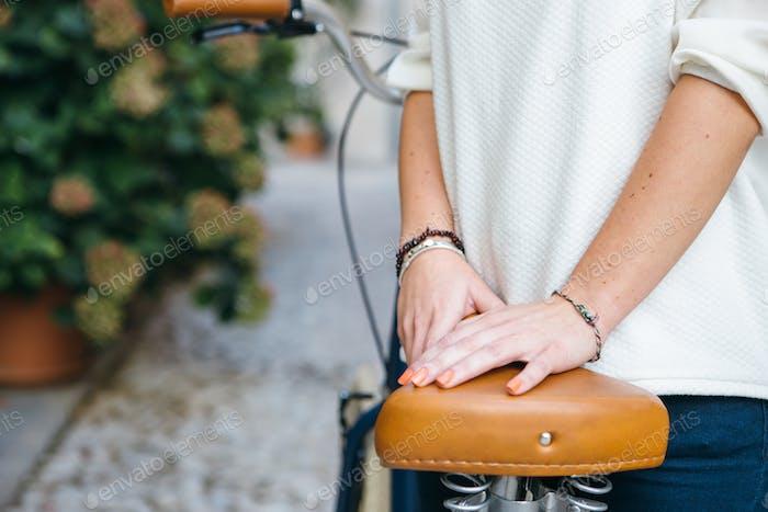 Crop weiblich posiert mit Fahrrad