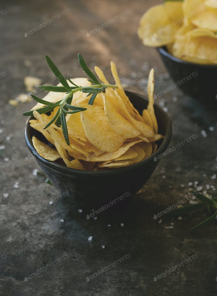 Crispy potato chips in ceramic bowls with salt and seasonings
