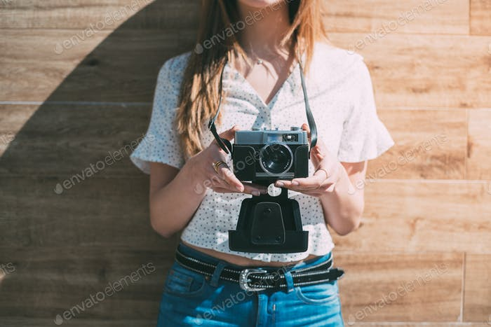 Cropped woman with vintage old camera