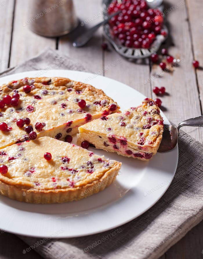 White chocolate cheesecake tart with cranberries on a white plate