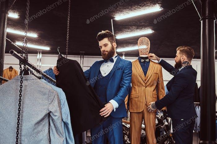 Два стильных продавщица элегантно одетых работают в магазине мужской одежды.